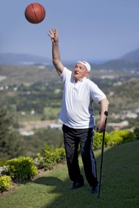 Old man shooting a basketball ball and looking to sky in the park